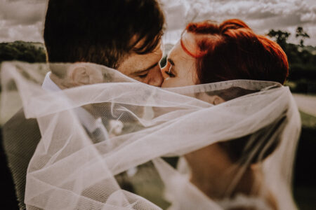Bride and groom kissing behind veil blowing in wind - Picture by Oobaloos Photography