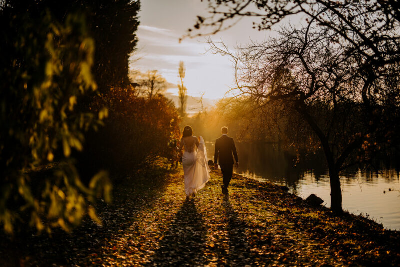 Bride and groom walking down leafy path by water as sun goes down - Picture by Kazooieloki
