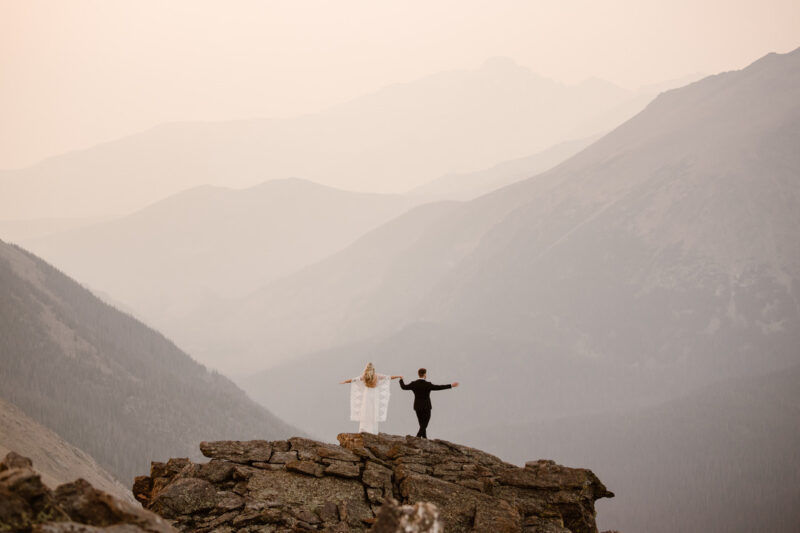 Bride and groom standing on rocks overlooking mountains - Picture by Adventure Instead
