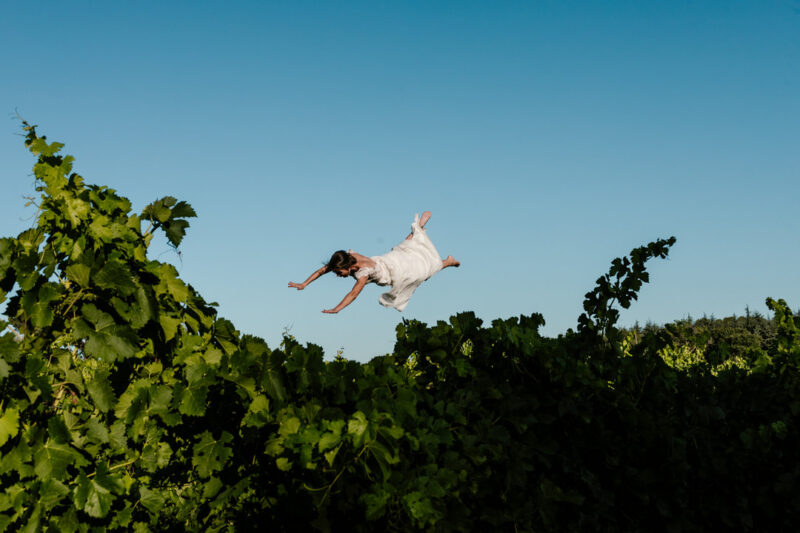 Bride flying through the air over bush - Picture by Alison Bounce Photography