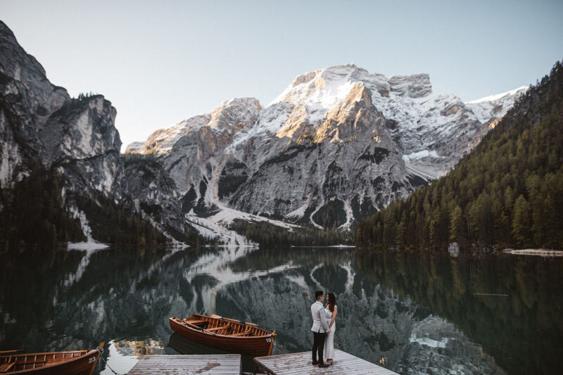 Bride and groom standing by lake with snow-covered mountains in background - Picture by Katja & Simon Photography