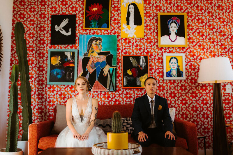 Couple sitting on sofa in front of colourful backdrop of patterned wallpaper and art - Picture by The Hendrys