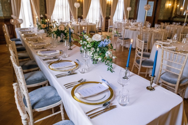 Wedding top table styled with gold rimmed plates and blue candles