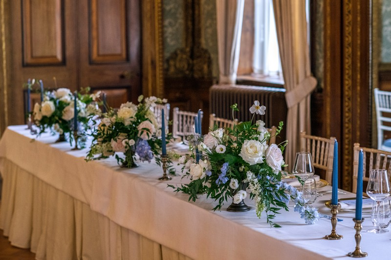 Wedding top table with floral displays of white and blue flowers with foliage