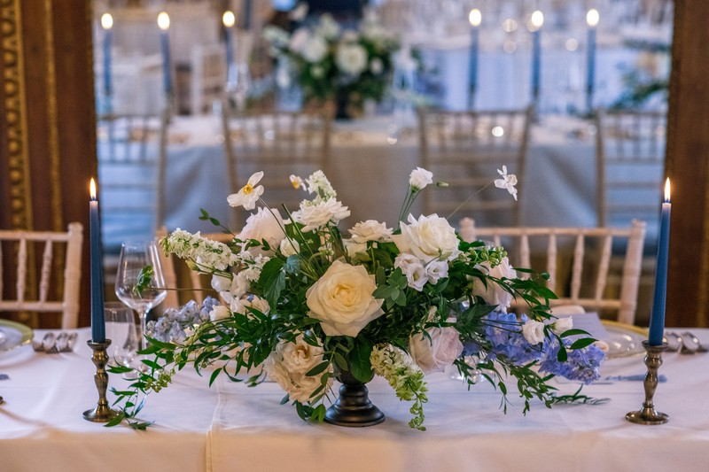 Floral wedding table display with blue and white flowers and foliage