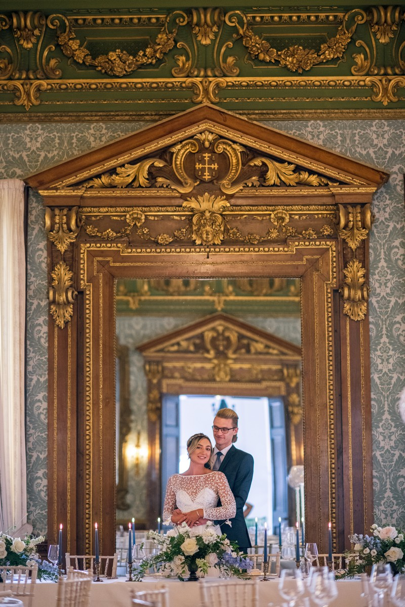 Bride and groom standing in front of mirror in The Ballroom at Hawkstone Hall