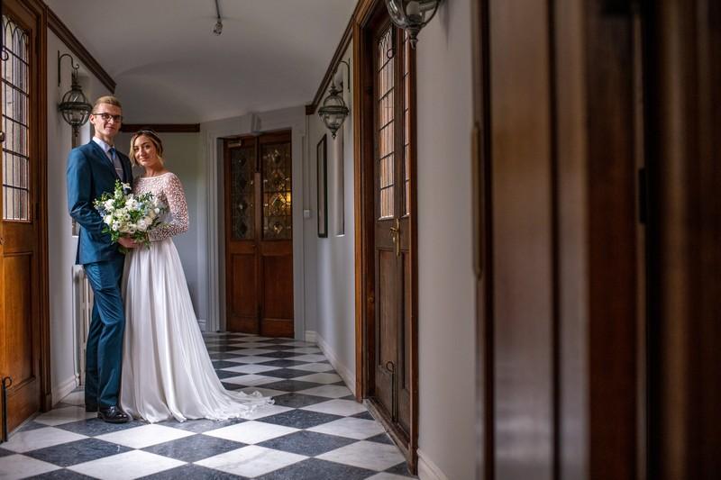 Bride and groom in corridor of Hawkstone Hall