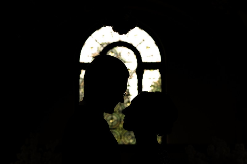 Silhouette of bride and groom's heads against window