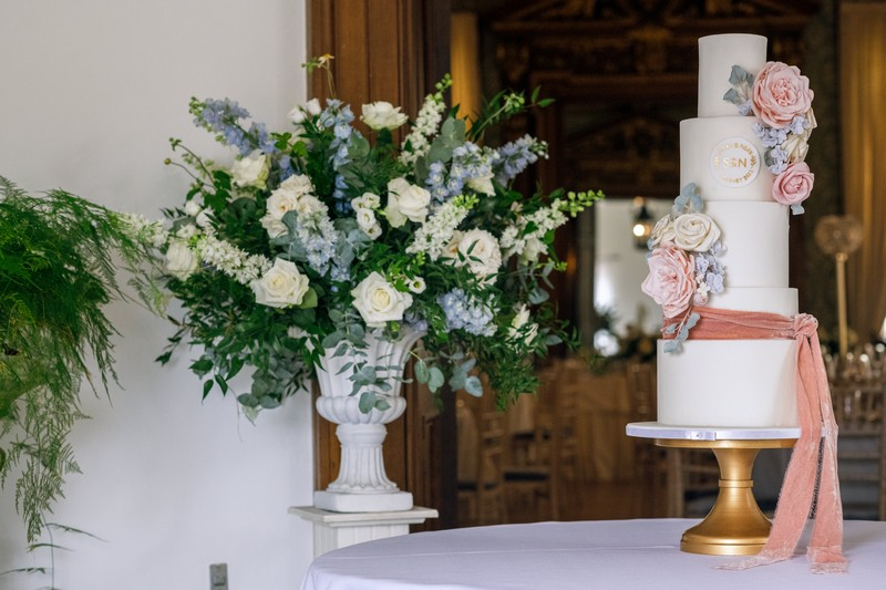 Wedding cake next to large blue and white floral display