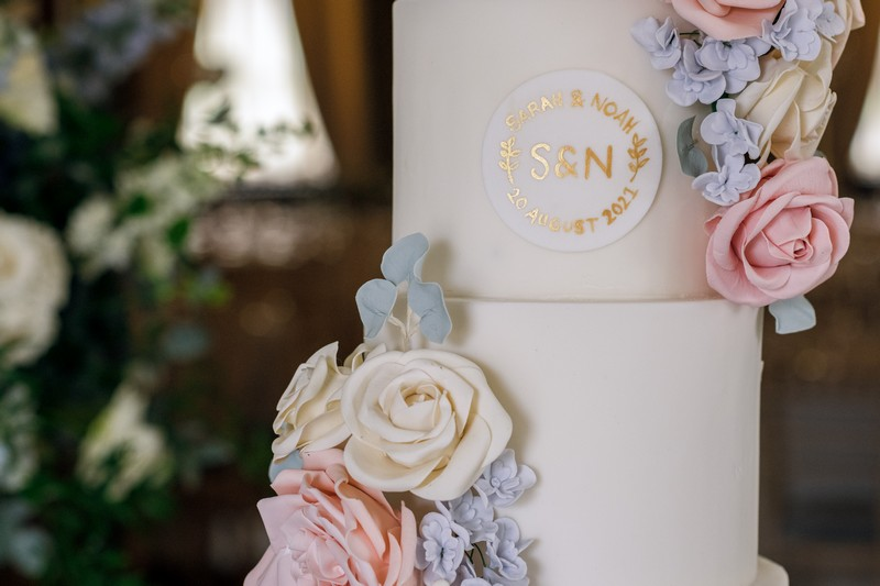 Wedding cake with motif and blue, ivory and pink sugar flowers