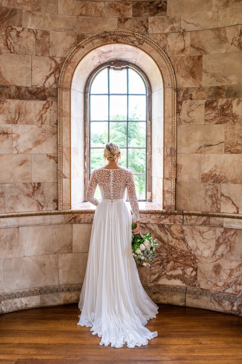 Bride looking out of window of The Tapestry Room at Hawkstone Hall