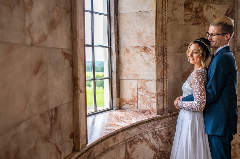 Bride and groom looking out of the window of The Tapestry Room at Hawkstone Hall