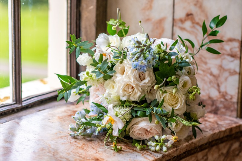 Bridal bouquet with ivory and blue flowers and green foliage
