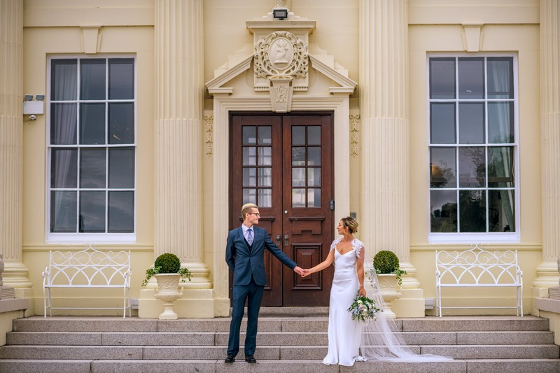 Bride and groom holding hands on steps of Hawkstone Hall