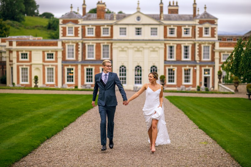 Bride and groom walking down driveway at Hawkstone Hall