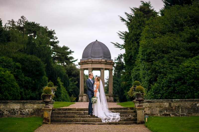 Bride and groom in front of stone gazebo at Hawkstone Hall