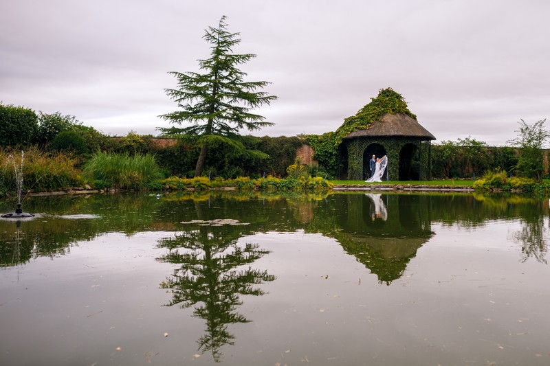 Bride and groom by pond at Hawkstone Hall
