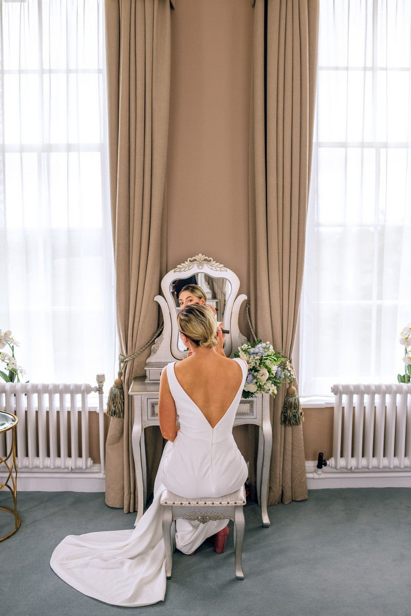 Back of bride sitting at mirror doing make-up
