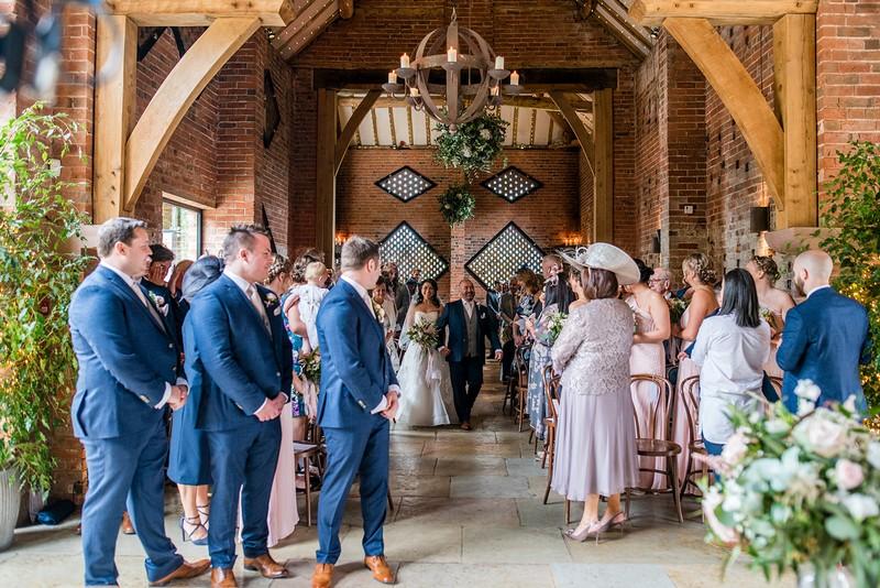 Bride walking down the aisle for wedding at Shustoke Barn