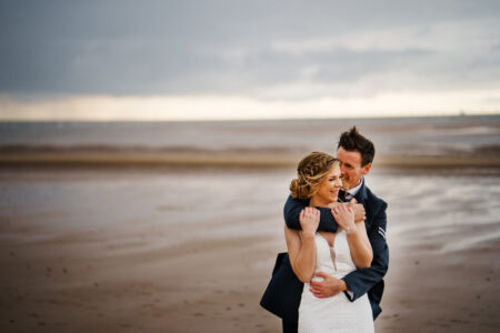 Groom hugging bride from behind on beach - Rob Dodsworth Photography