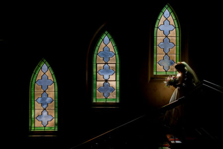 Bride walking down stairs past stained glass windows - Picture by Damion Mower Photography