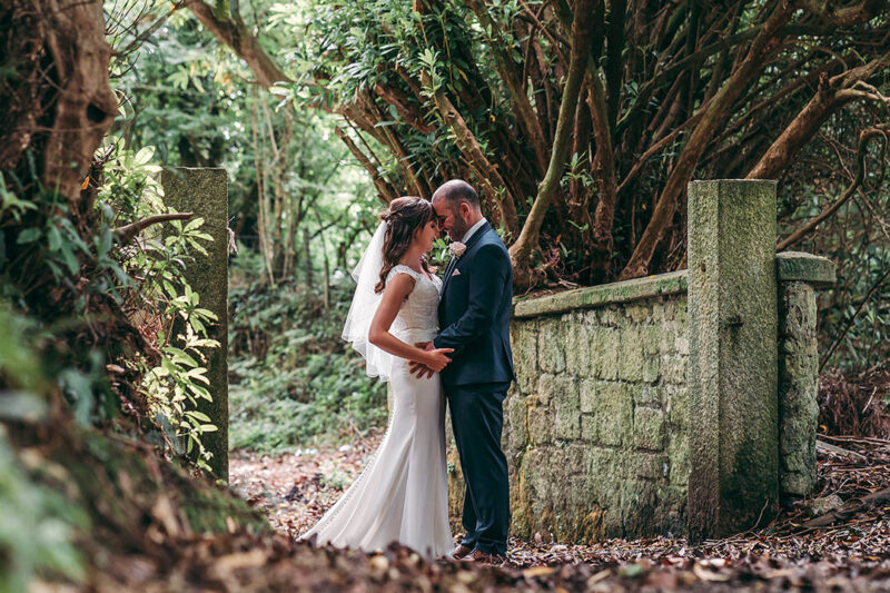 Bride and groom touching heads in woodland area with leaves on ground - Picture by Tracey Warbey Photography