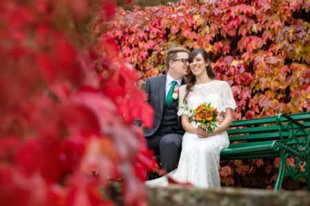 Bride and groom sitting on bench by bushes with red leaves - Picture by Helen England Photography