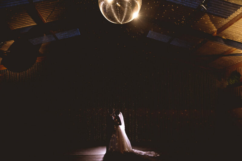 Bride and groom first dance in dark under glitter ball - Picture by Katie Sidell Photography