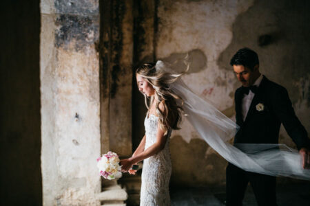 Groom standing behind bride holding end of her veil - Picture by Daniel López Pérez
