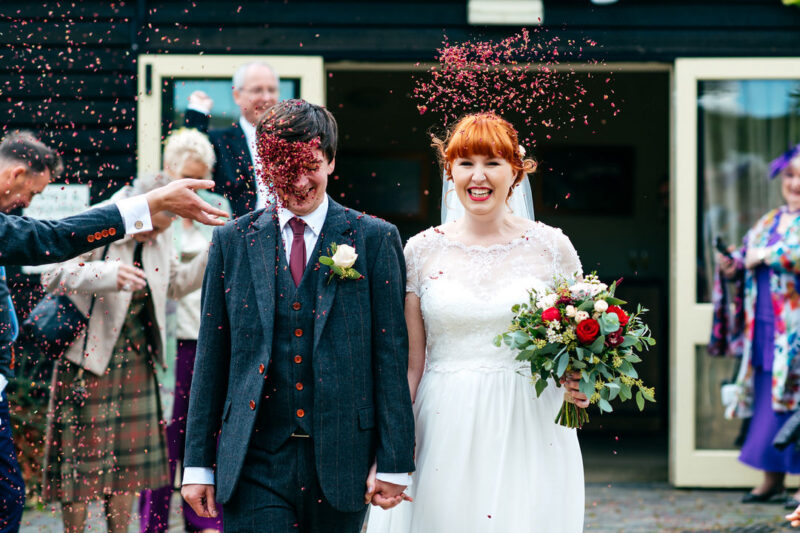 Groom being hit in face with confetti as he walks with bride - Picture by Jordanna Marston Photography