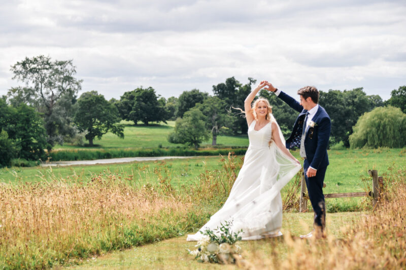 Bride twirling under groom's arm in field - Picture by Memories and Milestones Photography