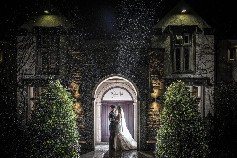 Bride and groom standing in doorway of Mitton Hall in rain at night - Picture by Peter Anslow Photography