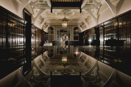 Bride and groom standing in room with their image reflected below them - Picture by Murray Clarke