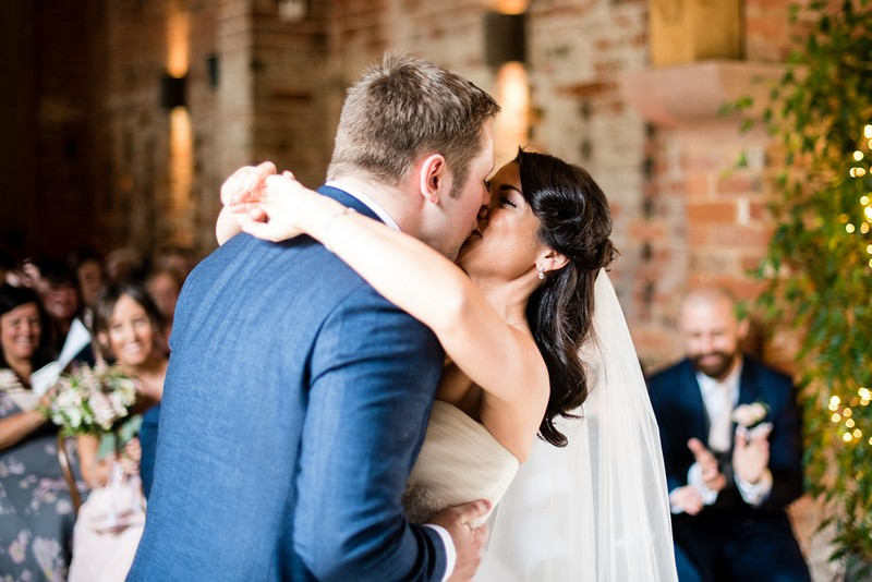 Bride and groom kiss at end of wedding ceremony