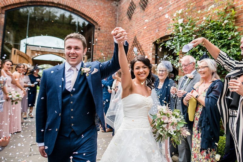 Bride and groom raising arms in confetti shower