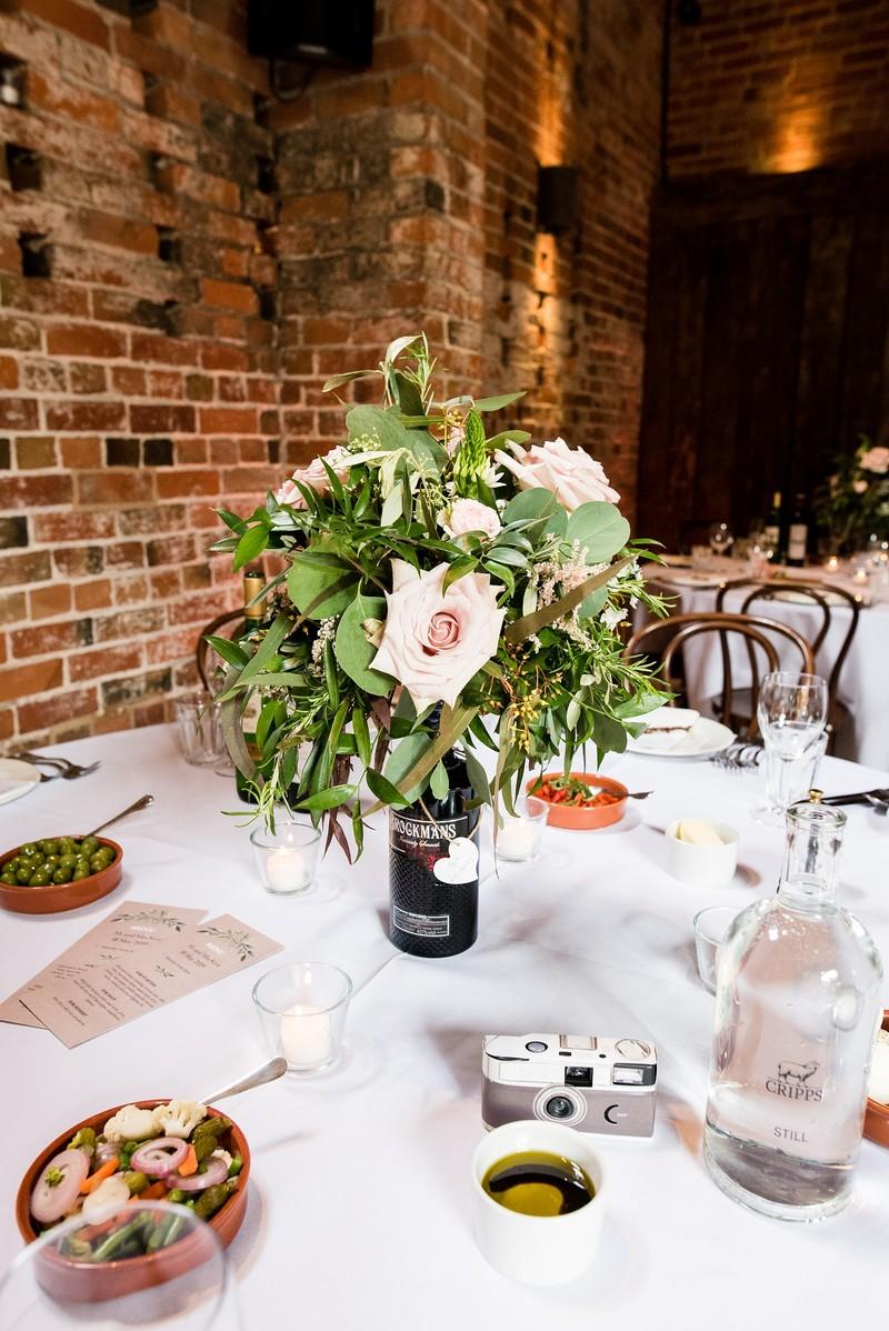 Wedding table flowers in gin bottle