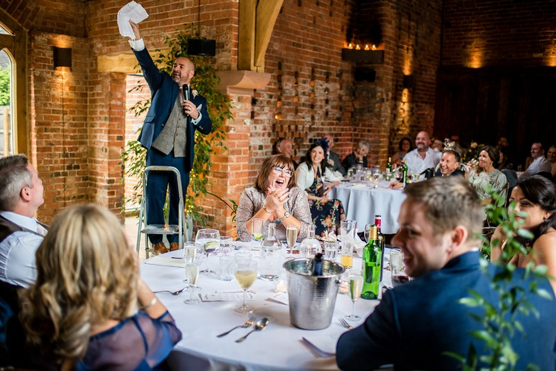 Man standing on step ladder to give wedding speech