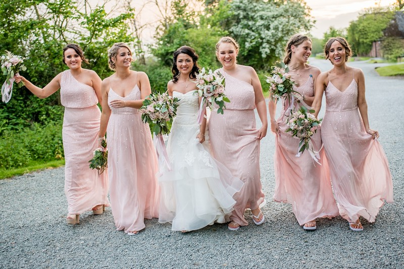 Bride walking with bridesmaids in pink dresses