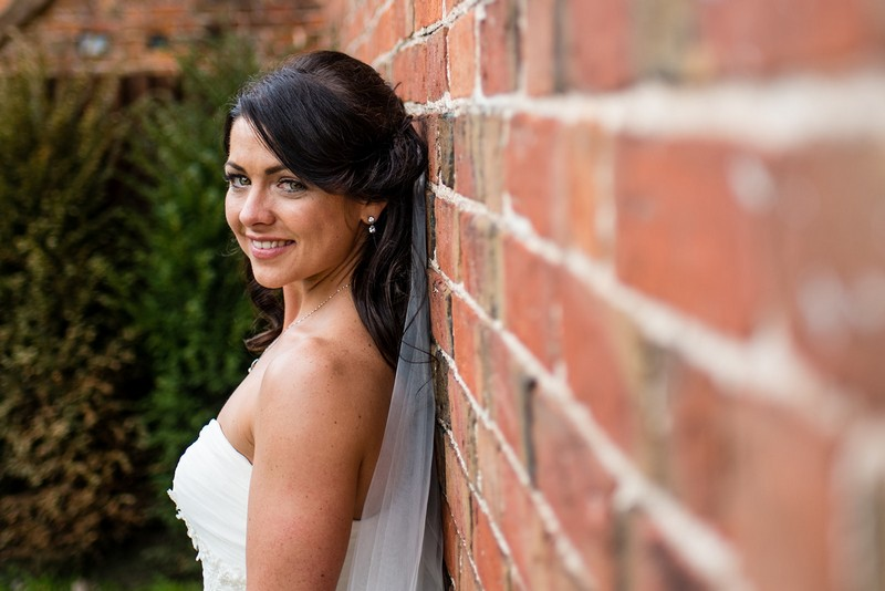 Bride standing with back to wall