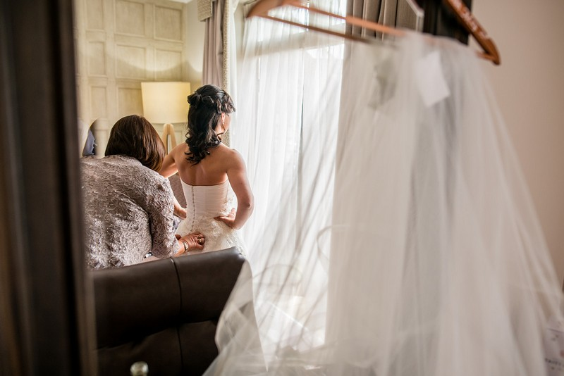 Reflection in mirror of woman doing up back of bride's wedding dress