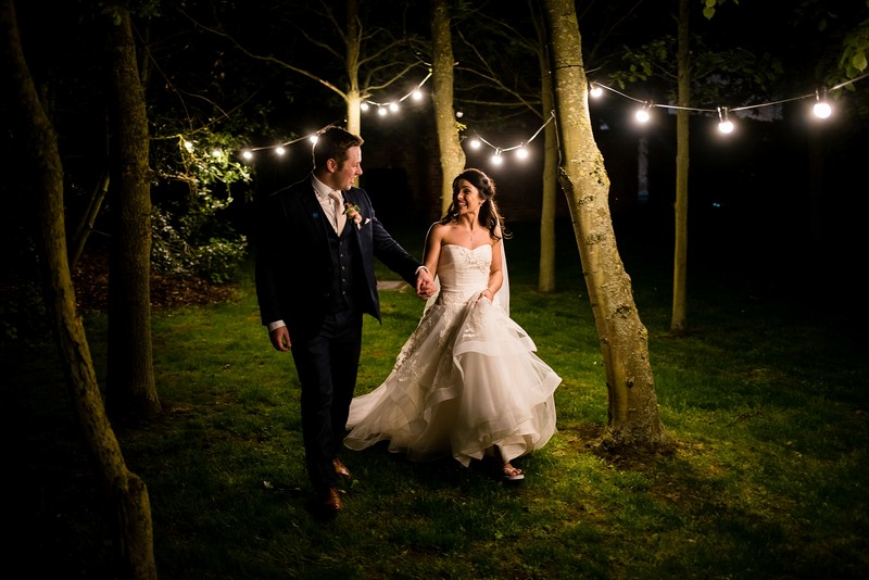 Bride and groom walking past trees at night