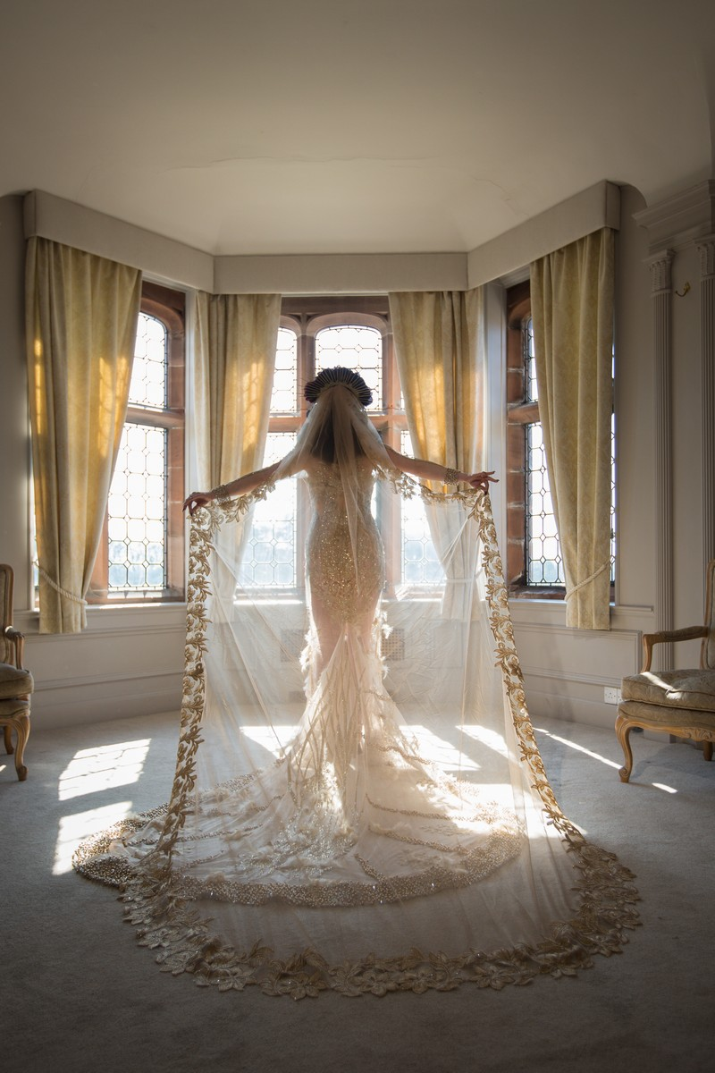 Bride holding out long veil behind her