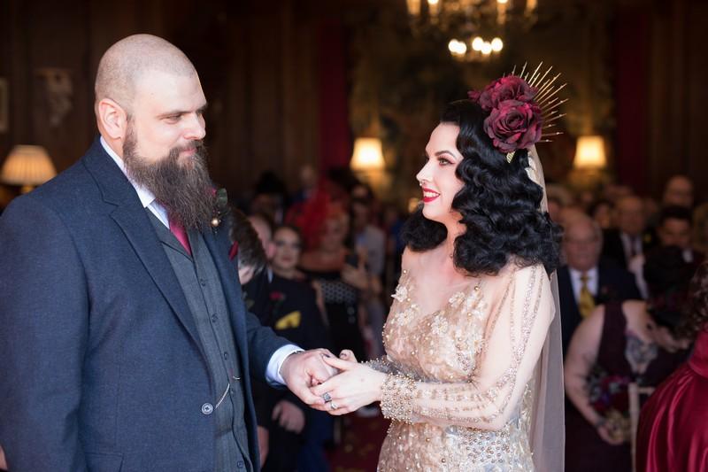 Bride holding groom's hand during wedding ceremony