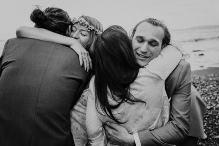 Bride and groom hugging friends on the beach - Picture by Alexa Poppe Wedding Photography