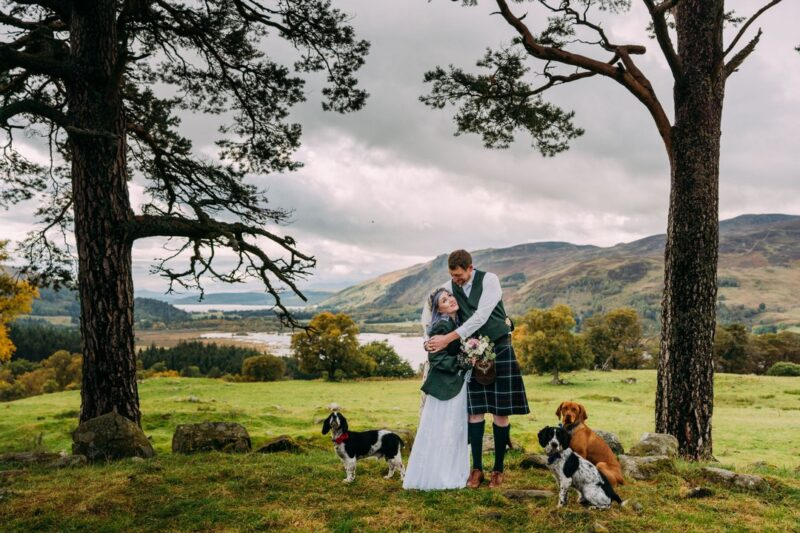 Bride and groom hugging in front of Scottish hills with their dogs - Picture by Eilidh Robertson Photography