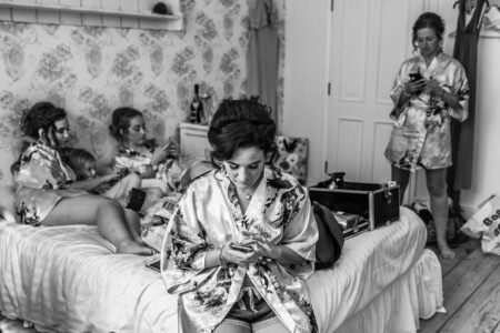 Bridesmaids all looking at their phones during bridal prep - Picture by Piccolino Weddings