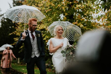 Bride and groom walking with umbrellas - Picture by BGS Weddings