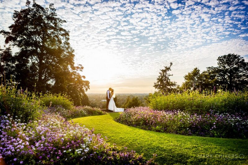 Bride and groom in beautiful garden with blue sky and clouds above - Picture by Mark Chivers Photography
