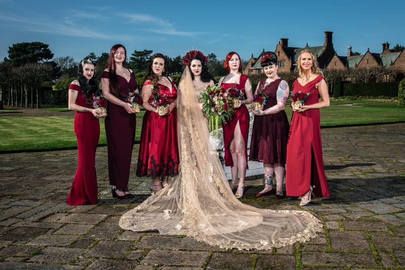 Gothic bride with bridesmaids in red dresses