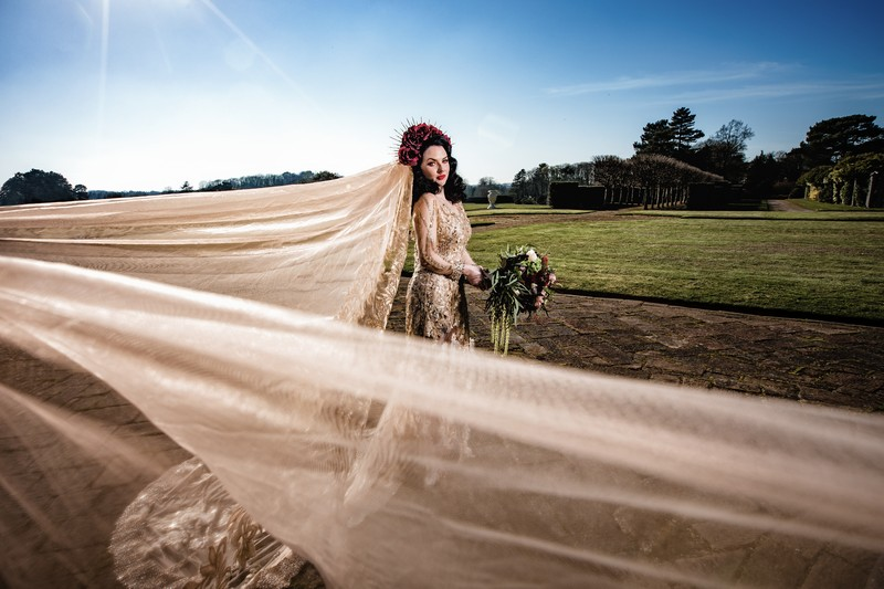 Bride's large veil blowing in wind behind her
